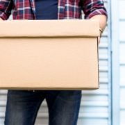 man holding box in front of storage unit
